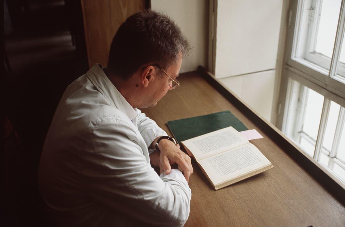 Opiskelu. Opiskelija lukemassa lukusalissa. Tutkija lukee. Akateeminen koulutus. Mies.