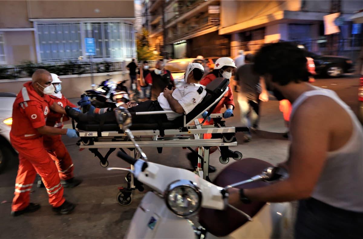 Lääkintähenkilökunta vie loukkaantuneita sairaalaan.