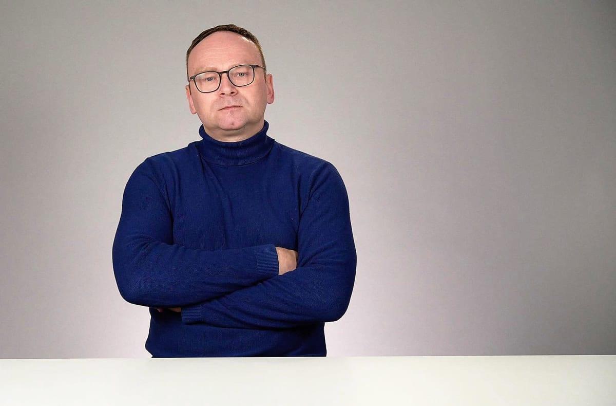 Fjodor Krasheninnikov seisoo vaaleaa taustaa vasten tummansinisessä korkeakauluksisessa villapaidassa. Hänellä on silmälasit.