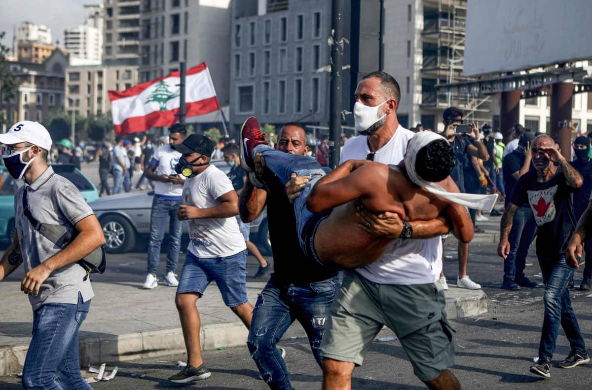 Mielenosoittaja kantaa haavoittunutta toveriaan turvaan Beirutin mellakoissa 8.8.2020.