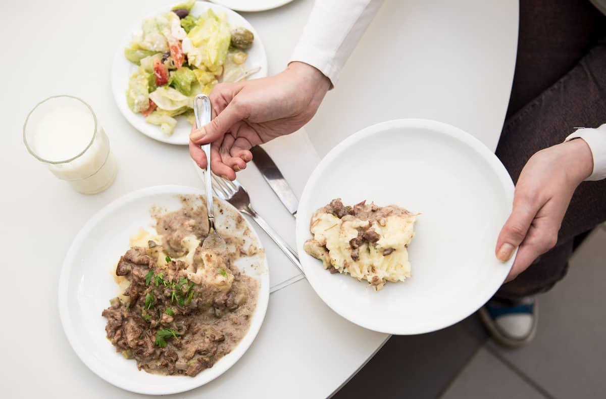 NAinen siirtää ruokaa lautaselta lautaselle.