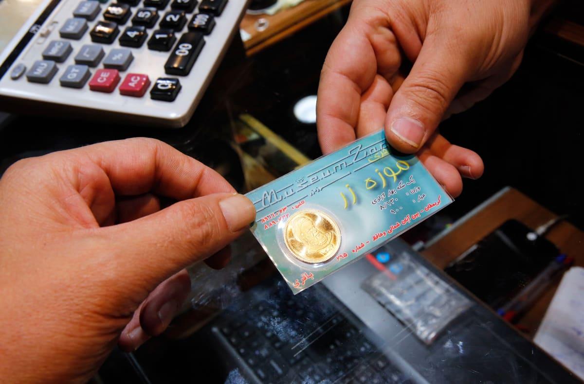 Kultakolikkoa ojennetaan kaupassa Teheranissa Iranissa.