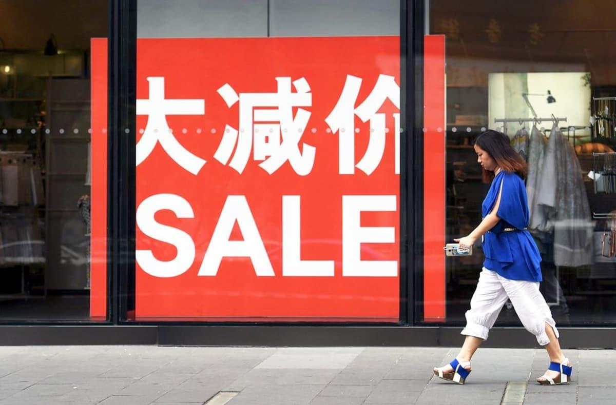 Nainen kävelee alennusmyynti-kyltin ohi Pekingissä heinäkuussa 2015.