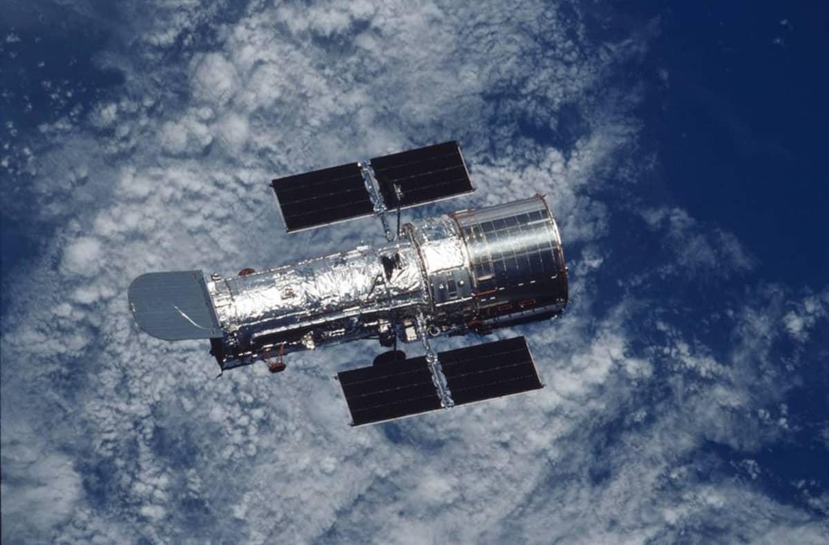 Hopeisena hohtava Hubble aurinkopaneeleineen ja peileineen. Alla maapallon pilvipeitteistä sinistä pintaa.