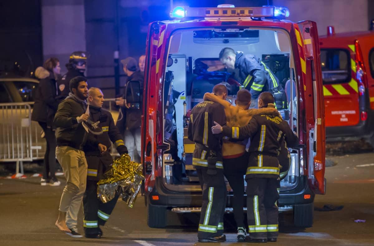 Pelastushenkilöstö saattaa ampumavälikohtauksessa loukkaantuneita ihmisiä ambulanssiin Pariisin keskustassa myöhään perjantai-iltana.