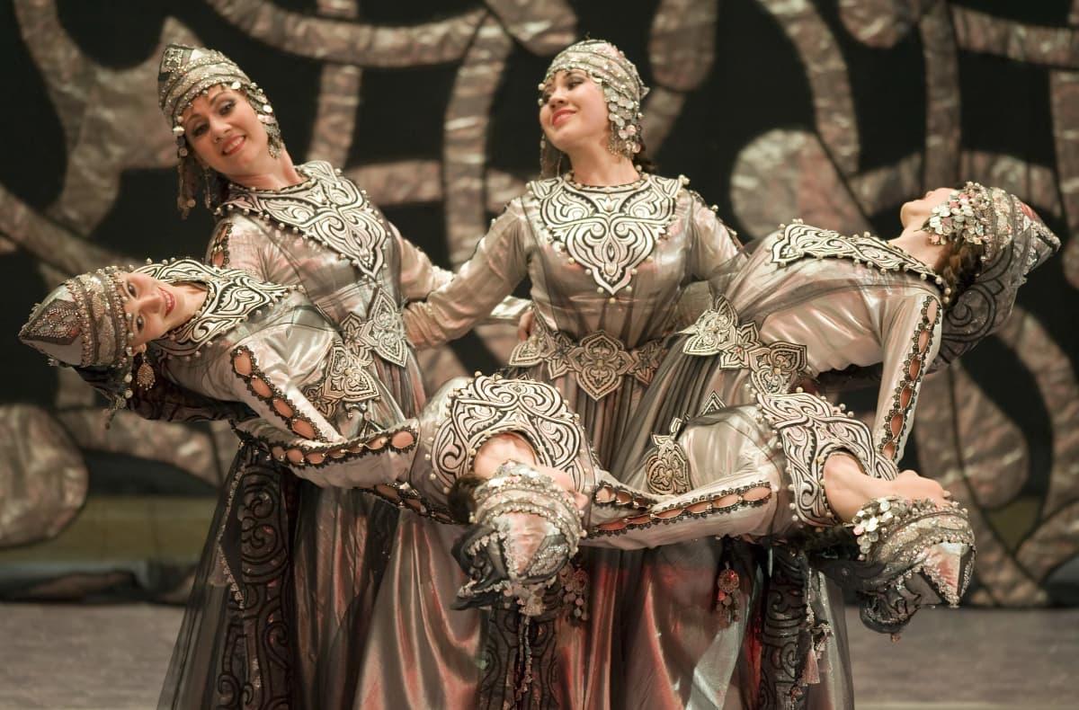 Kansallisasuisia naisia tanssimassa.