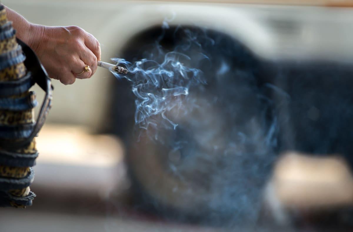 Lähikuva naisen kädestä, jossa savuaa tupakka.