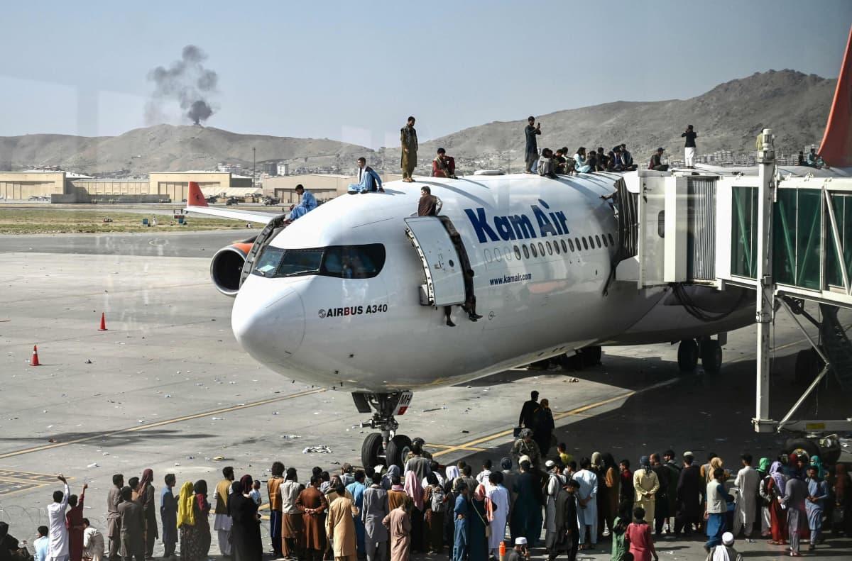Ihmisjoukko seisoo pysähtyneen lentokoneen päällä Kabulin lentokentällä.