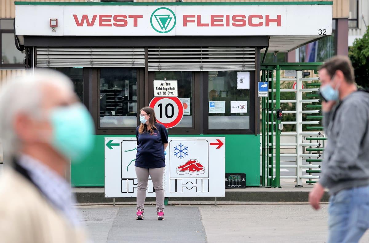 Ihmisiä kulkee Westfleisch-elintarviketehtaan portilla suojaimet kasvoillaan.