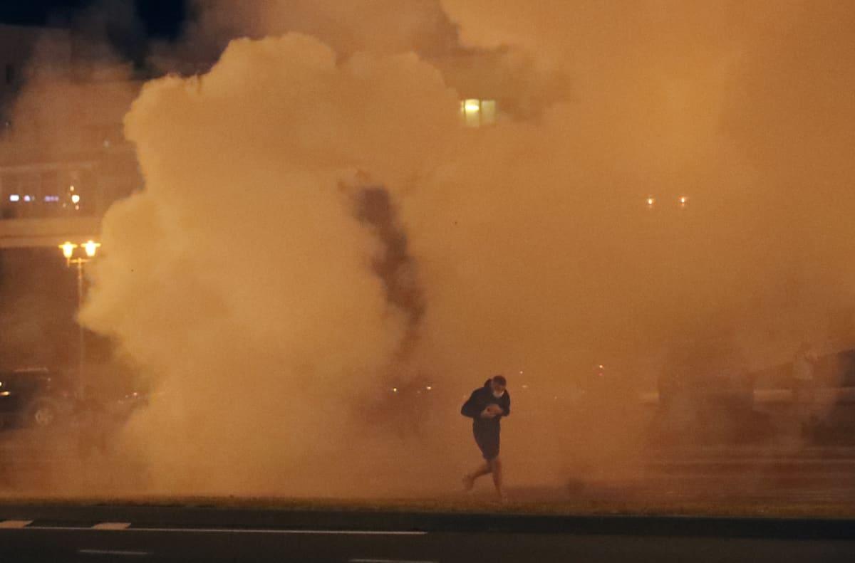 Mielenosoittaja juoksee läpi kyynelkaasupilven Minskissä 9. elokuuta 2020.
