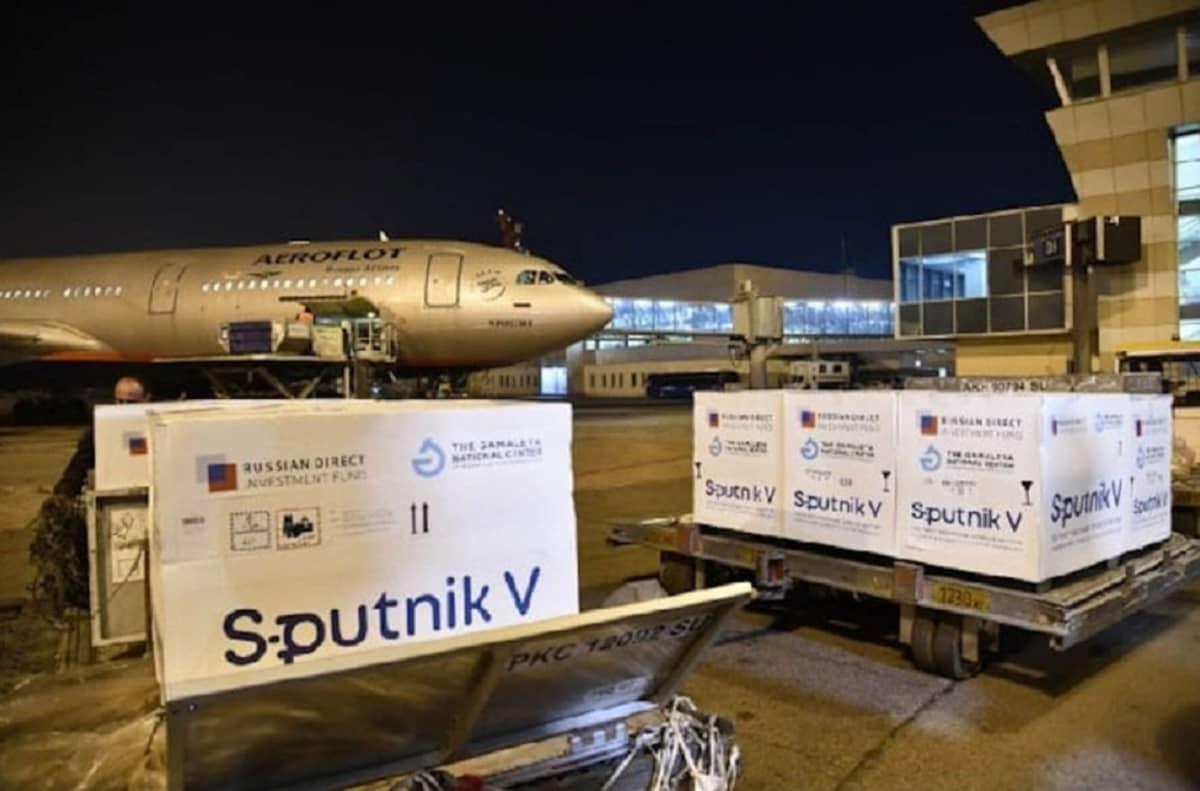 Kuvassa laatikoita, joissa lukee teksti Sputnik V. Taustalla näkyy lentokone.
