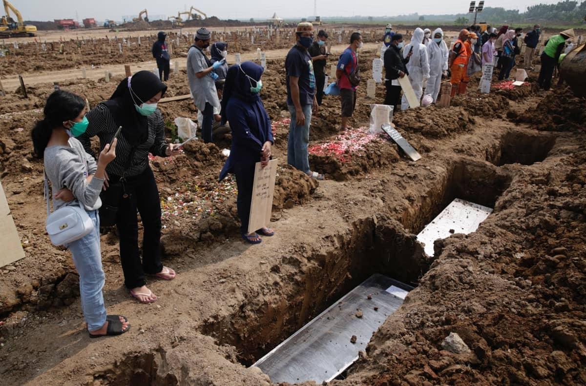 Avonaisia hautoja, omaisia hautojen äärellä.