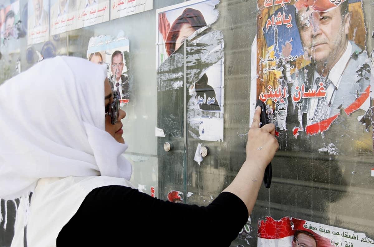 Valkoiseen huiviin pukeutunut nuori nainen raaputtaa vaalijulistetta harmaasta seinästä. Julisteessa on miehen kasvot ja arabiankielistä tekstiä.l