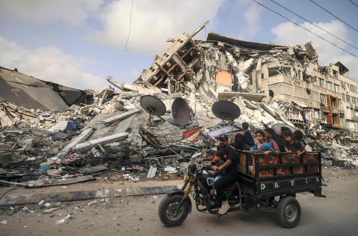 Palestiinalaiset siviilit moottoriajoneuvon kyydissä raunioituneella kadulla.