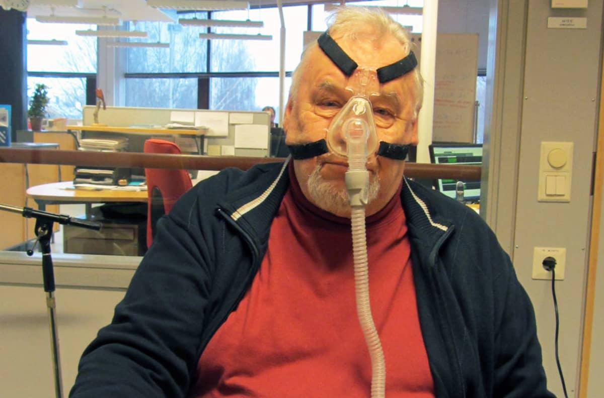 Erkki Tähtinen ja CPAP-laitteen maski.