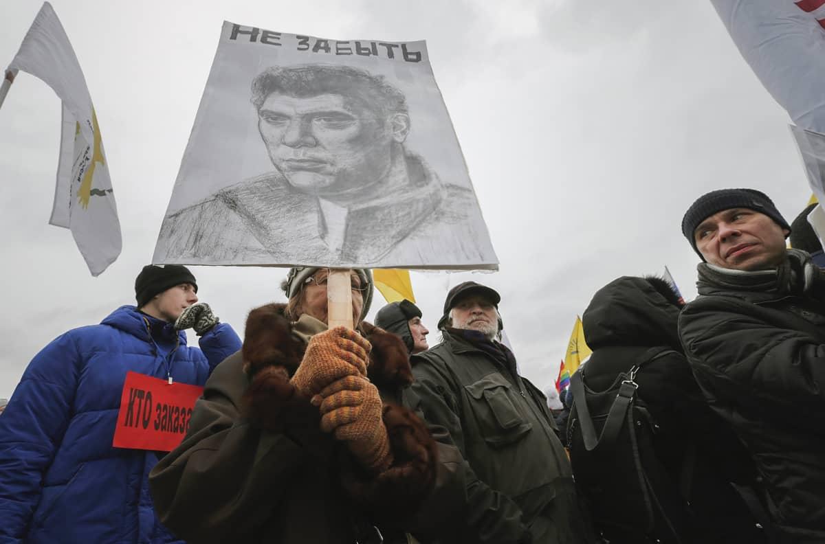 Nainen pitelee kylttiä johon piirretty Boris Nemtsov kuva.