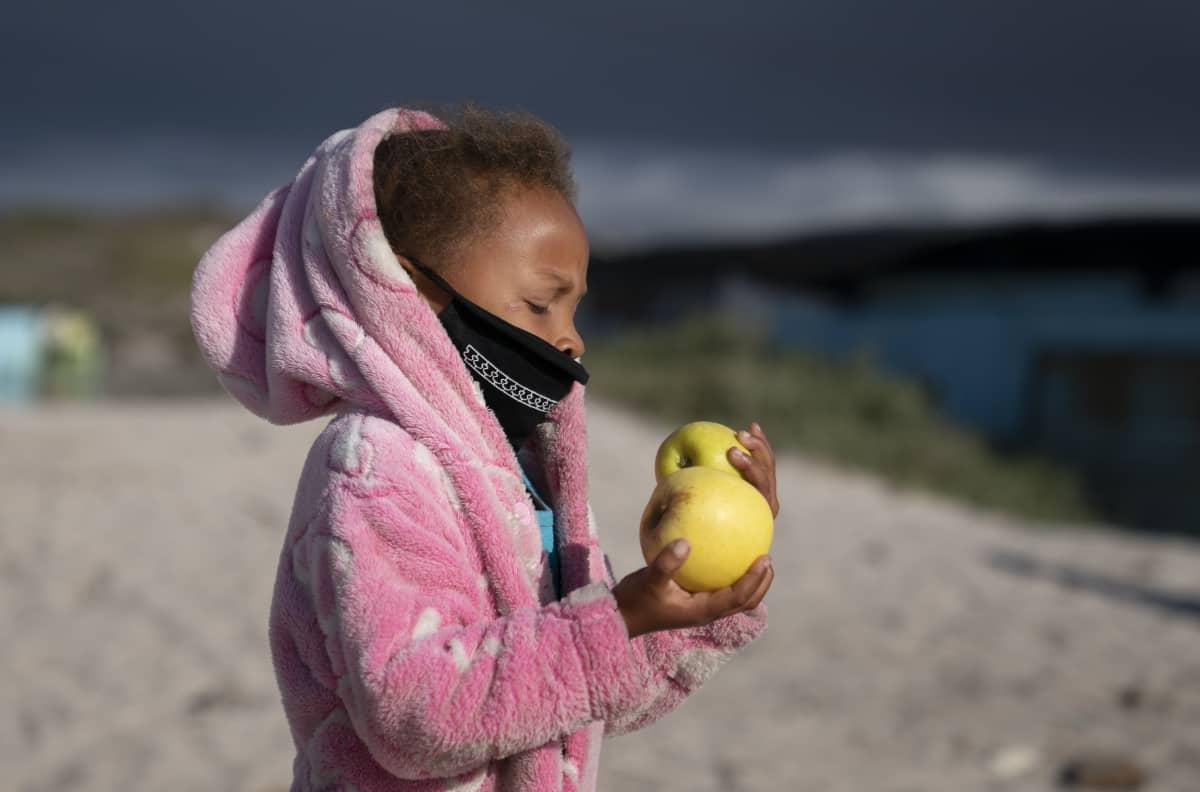 Kapkaupungissa lapsi on saanut avustusjärjestön ruoka-avusta omenan.