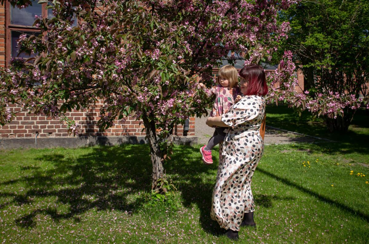 Tiia Trogen ihailee puun kukkia lapsensa Sofian kanssa.