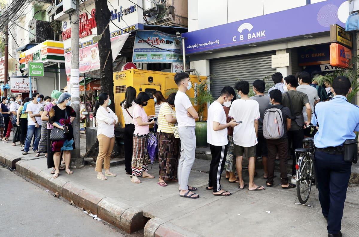 Ihmiset jonottavat pankkiautomaatille.