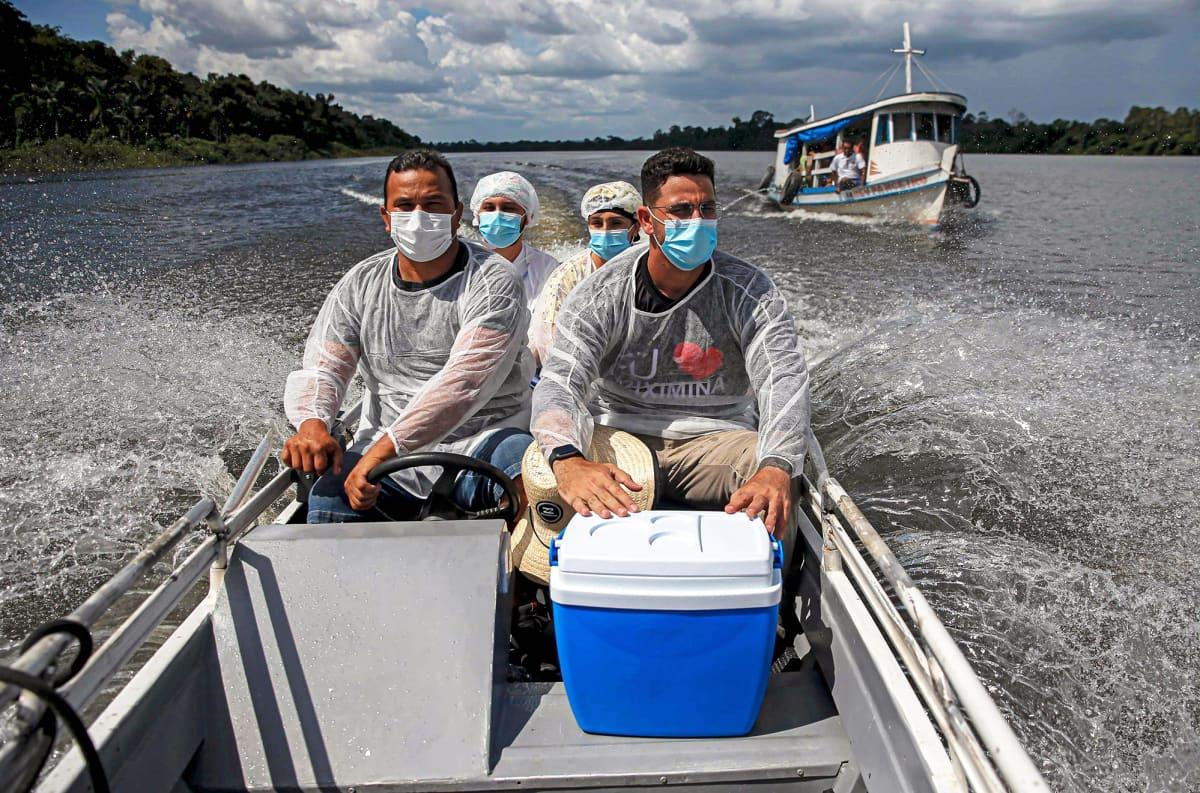Ryhmä terveydenhuollon työntekijöitä matkustaa pikaveneellä.