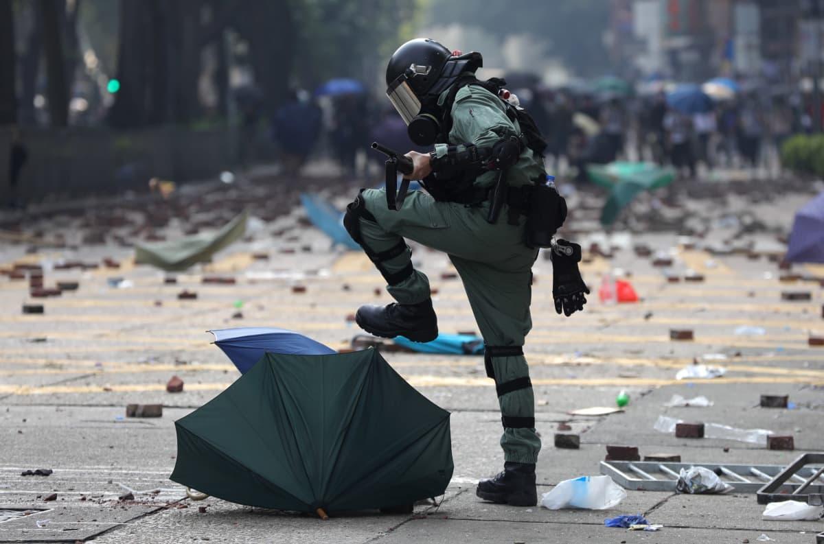 Mellakkapoliisi polkee sateenvarjoa.