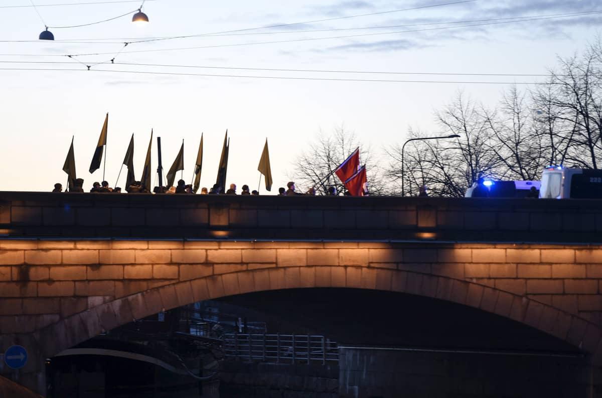 Uusnatsien Kohti vapautta! -marssi ylittämässä Pitkääsiltaa natsien hakaristilippujen kanssa Helsingissä itsenäisyyspäivänä.