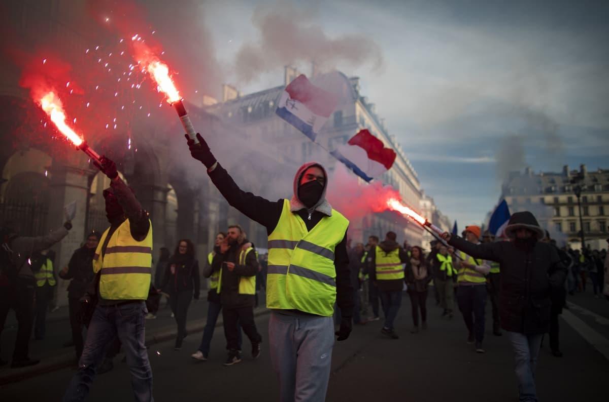 Keltaliiviset mielenosoittajat kävelevät kadulla soihdut kädessään.