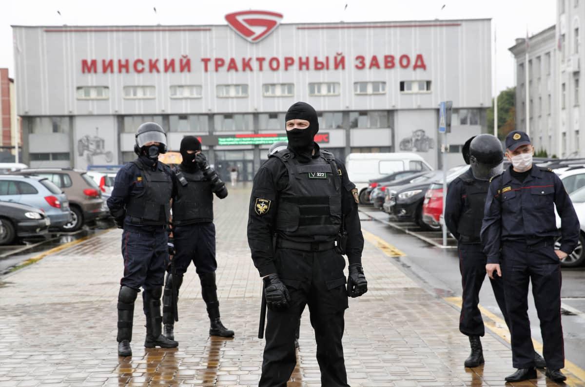 Joukko miliisin OMON-erikoisjoukkojen jäseniä seisoo Minskin traktoritehtaan edustalla tummissa univormuissa ja mellakkavarusteissa.