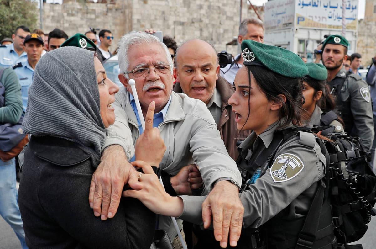 Mies erottamassa palestiinalaisnaista ja Israelin sotilasta