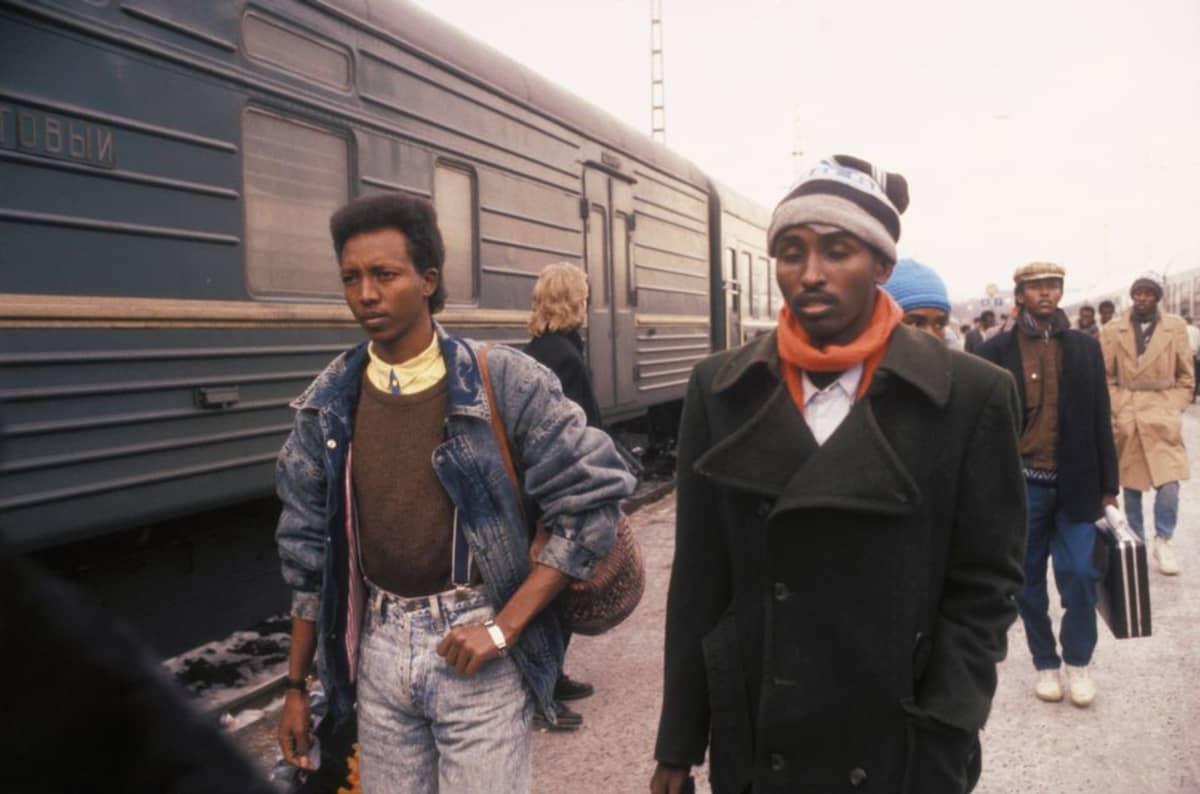 Nuoria somalimiehiä kävelee junan vieressä