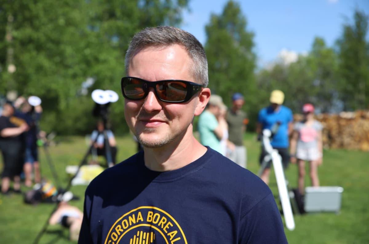 Mies seisoo aurinkolasit päässä