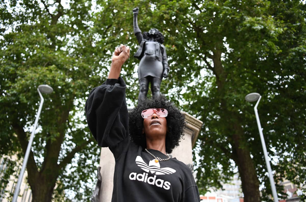 Jen Reid poseeraa itseään esittävän patsaan edessä samassa asennossa kuin veistos.