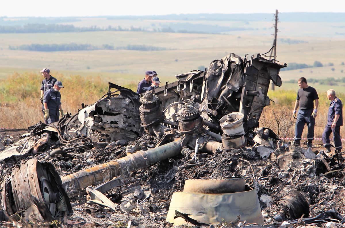 Pellolle kuvan etualalla on on tuhoutuneita lentokoneen osia. Kauempana seisoo miehiä.