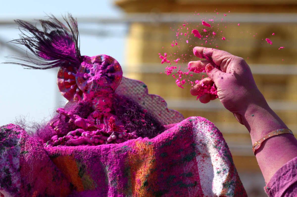 Nainen heittää punaista värijauhetta pienen Krishnan patsaan päälle Armitsarissa.