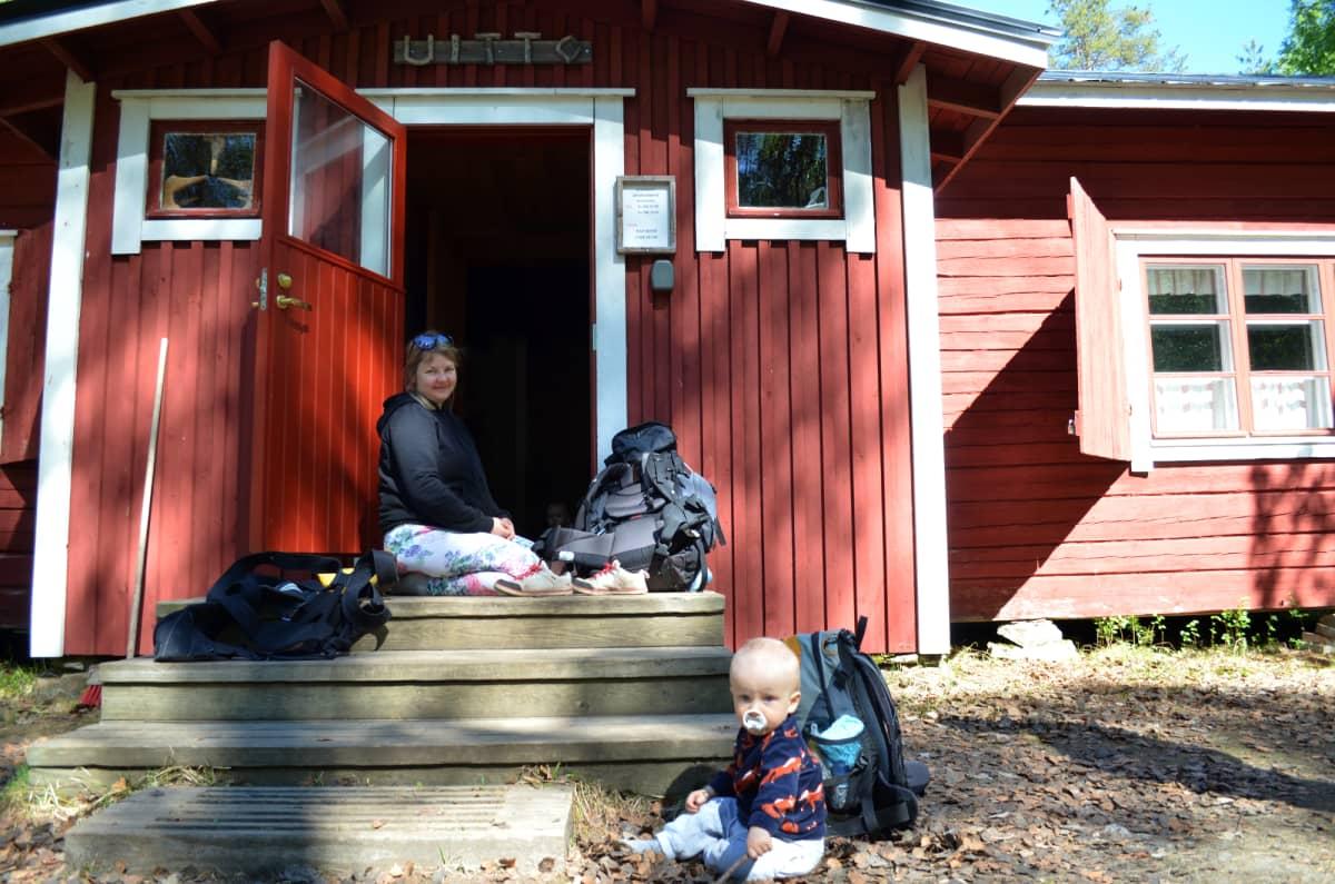 Nainen istuu mökin portailla ja maassa leikkii pieni poika