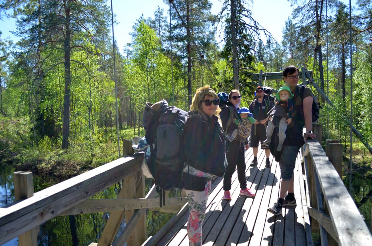 Neljä retkeilijää seisoo rinkat selässä puisella sillalla metsässä. Kahdella heistä on lapsi kantorepussa.
