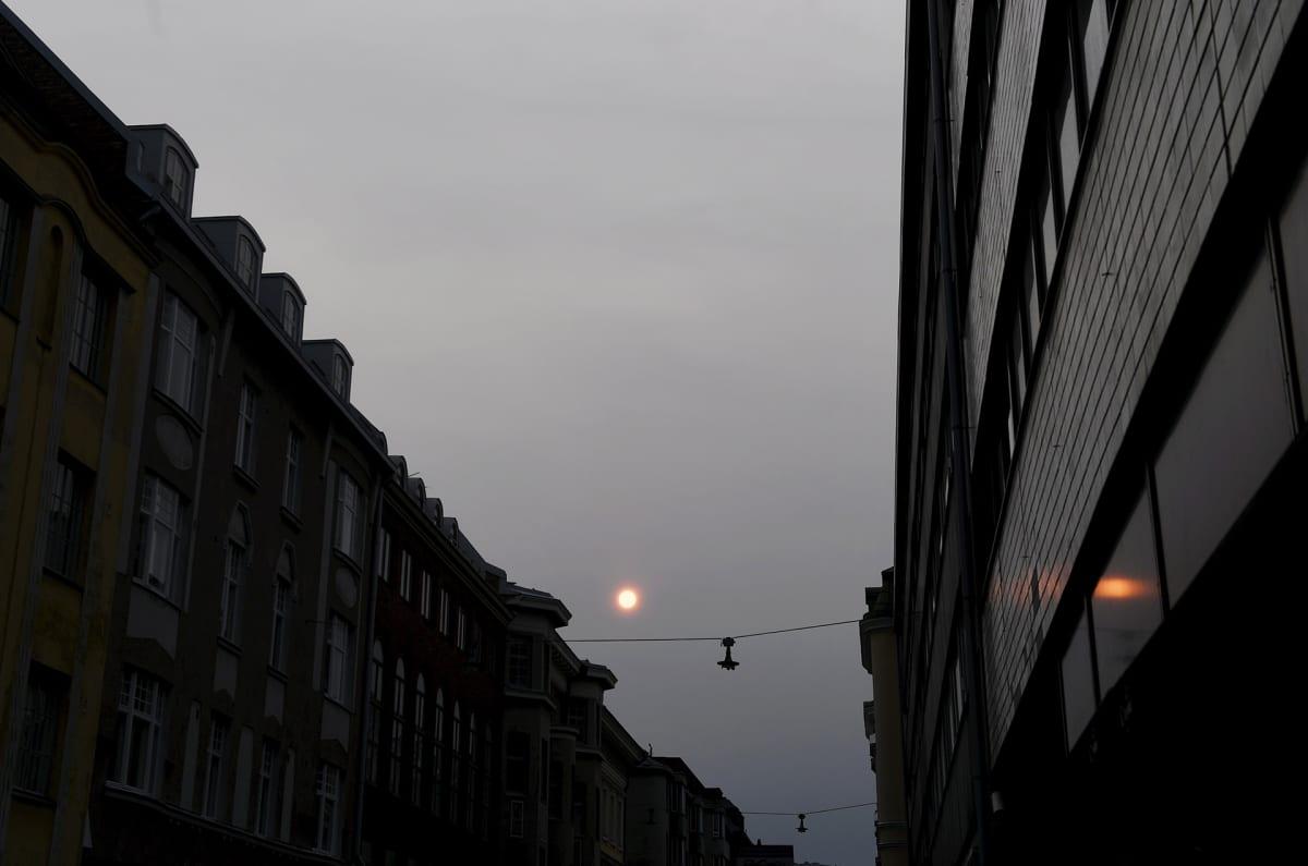 Aurinko hehkuu punertavana Helsingin keskustassa.
