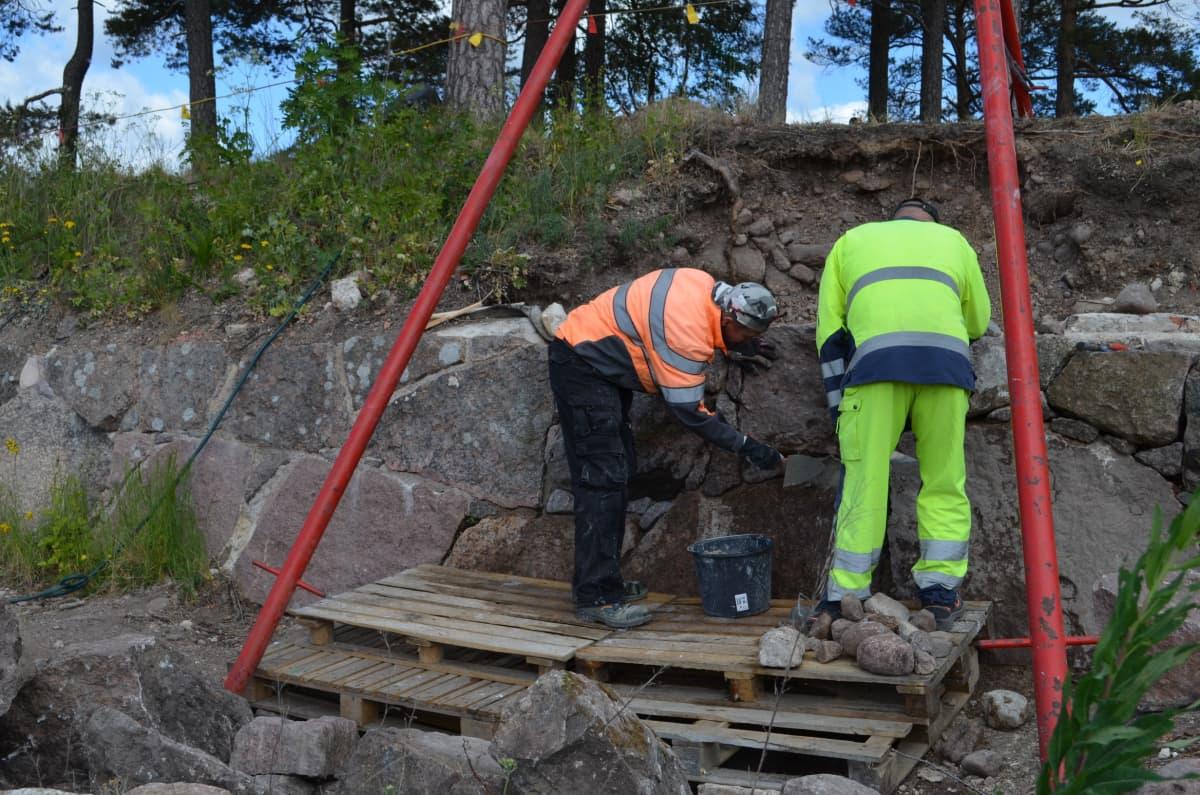 Kaksi miestä työskentelee muurin luona asettaen kiilakiviä isompien muurikivien väliin koloihin.