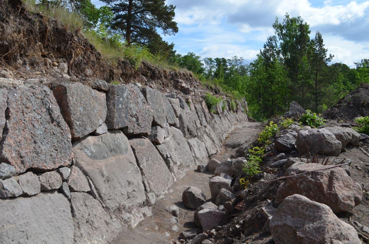 Linnoituksen kunnostamatonta muuria kaivettuna esiin maavallin alta.
