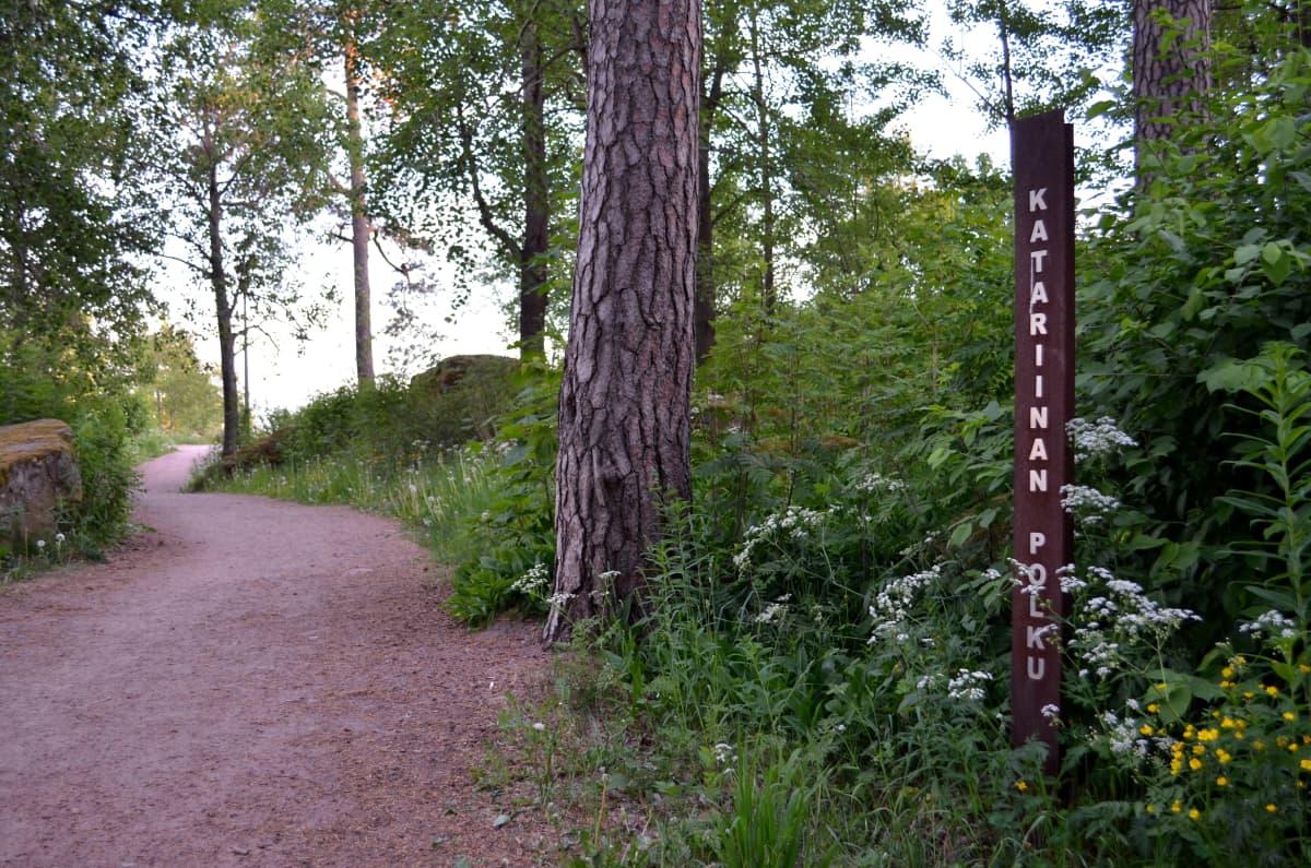Hiekkainen kävelypolku metsässä, tien vieressä iso mänty ja sen oikealla puolella Katariinan polku -kyltti.