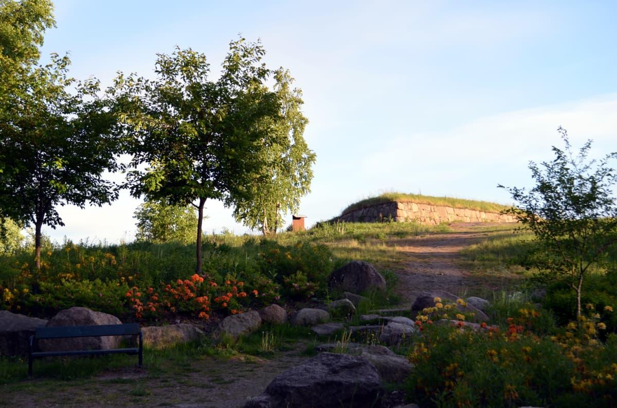 Linnoitusmuuria näkyy mäen päällä, edessä sinne johtava polku ja puiston istutuksia.