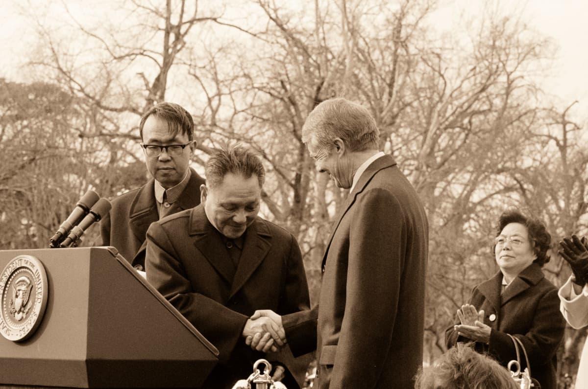 Deng kättelee Carteria. Miehet seisovat puhujanpöntön vieressä Valkoisen talon pihalla. Kuva on mustavalkoinen.