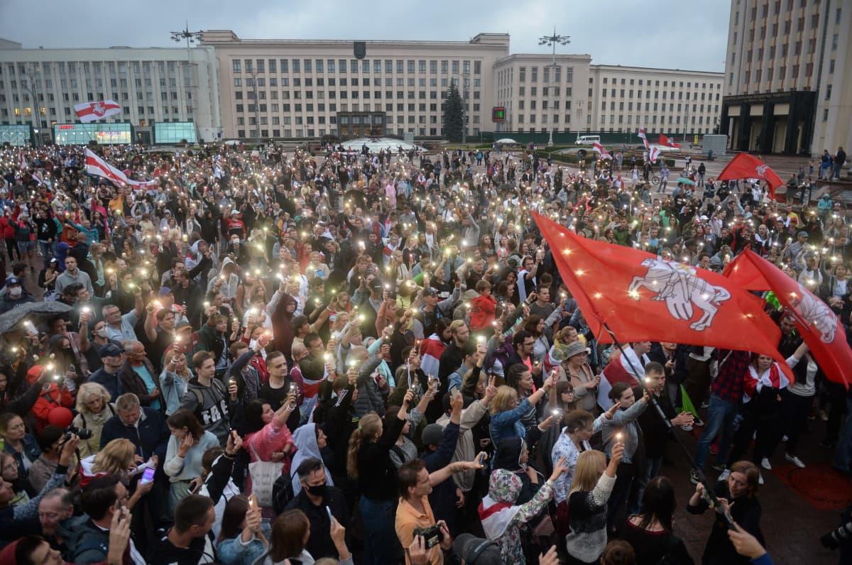 Suuri ihmismäärä täyttää neuvostotyylisten rakennusten ympäröimän aukion. Monet pitävät ylhäällä puhelimiaan lamput sytytettyinä.