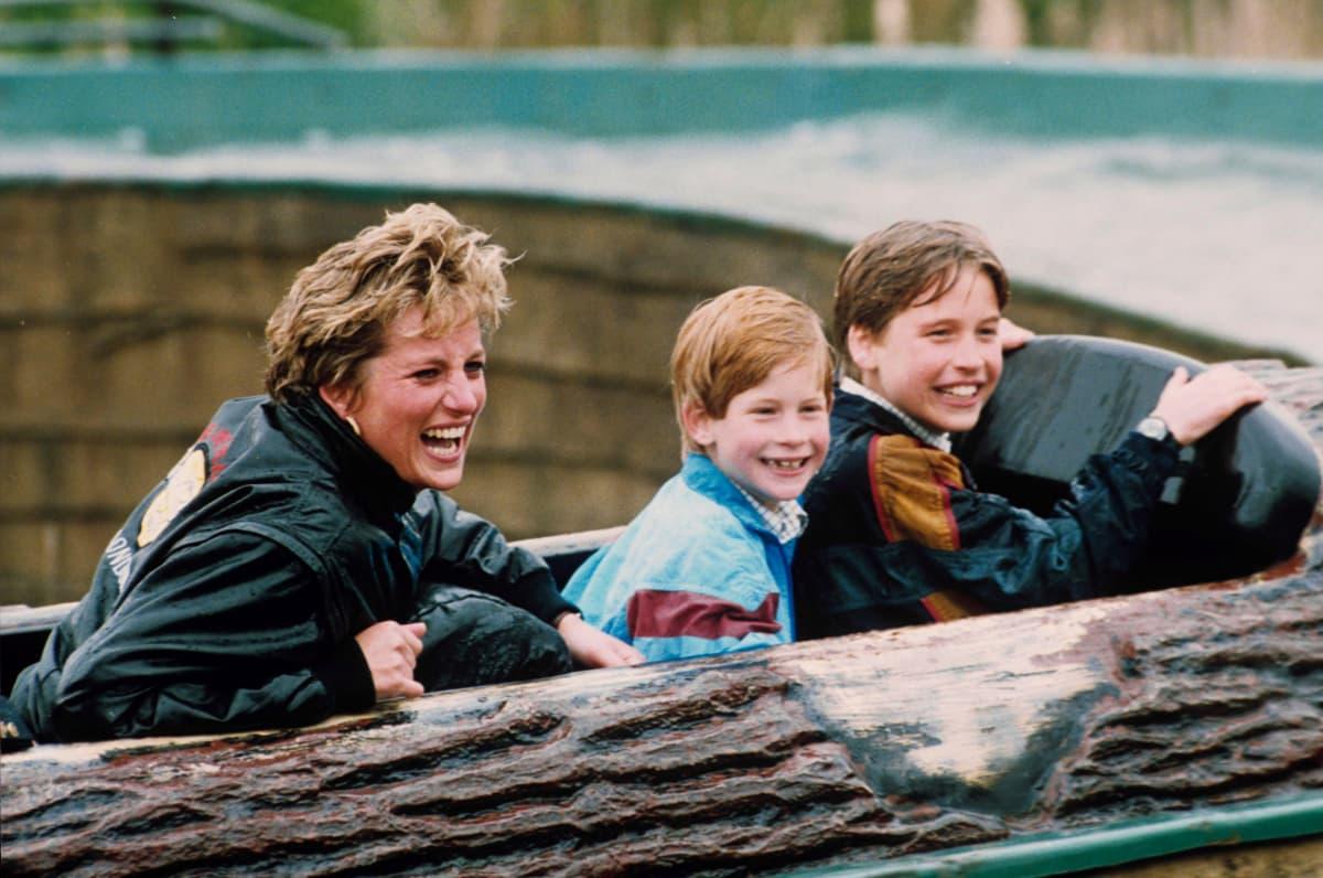 Diana ja pojat nauravat huvipuistolaitteessa.