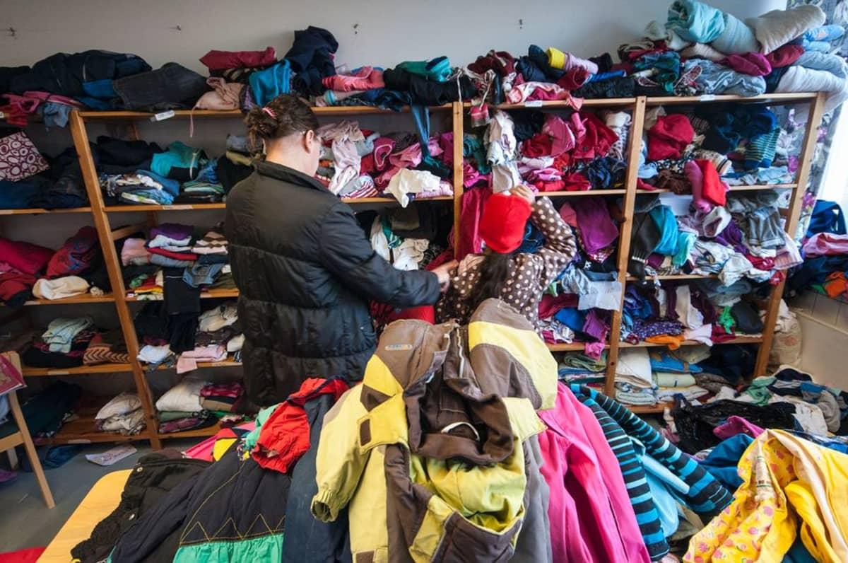 Lapsille etsitään sopivia vaatteita.