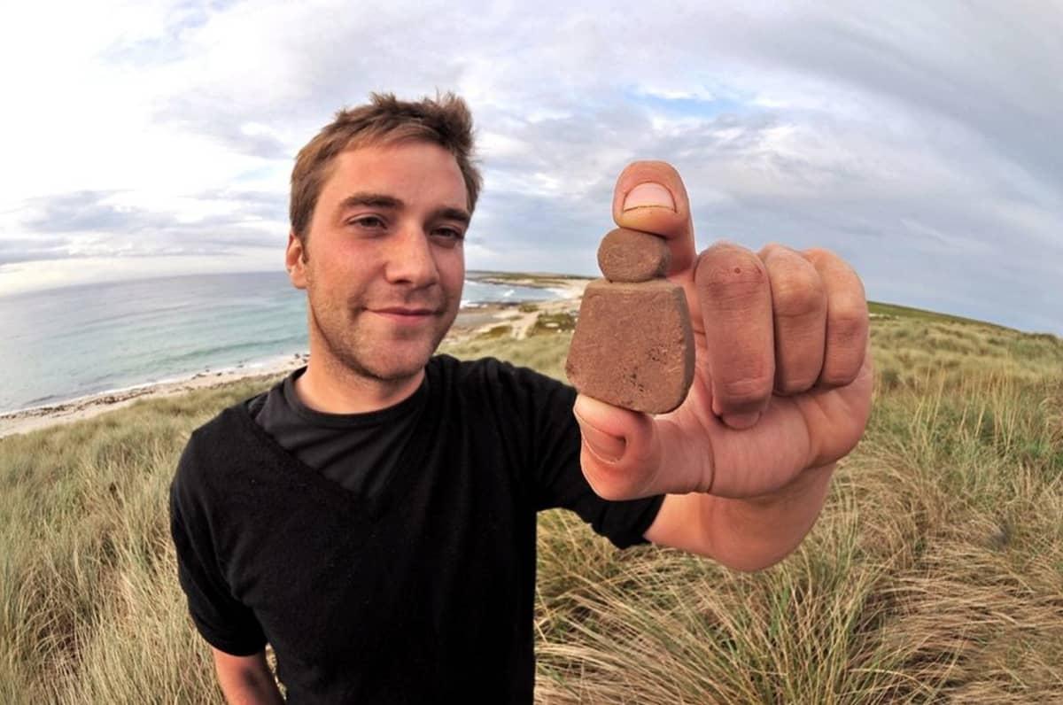 Arkeologi  Jakob Kainz pitelee peukalon ja etusormen välissä nelisenttistä patsasta. Taustalla skotlantilainen rantamaisema.