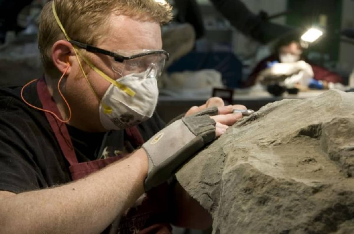 Suojalaseihin ja maskiin pukeutunut mies työtää kivikimpaletta.