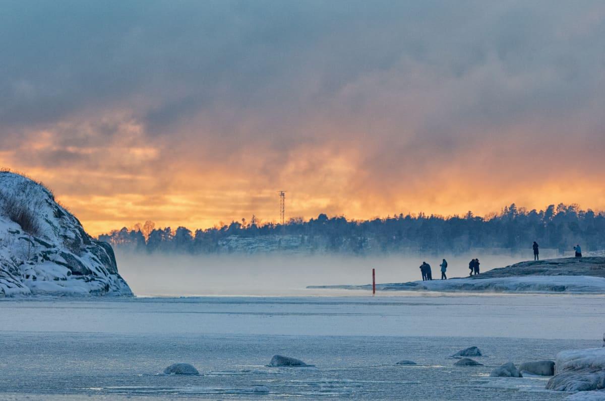 Ihmiset ihailevat merisumua ja auringonlaskua Helsingissä meren äärellä.