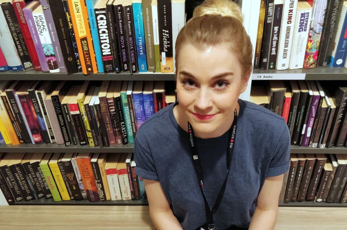Nuori nainen istuu kirjastohyllyn edessä ja katsoo suoraan kameraan.