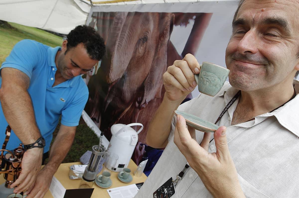 Turisti juo Black Ivory -kahvia kahvimerkin perustajan Blake Dinkinin tarjoilemana.